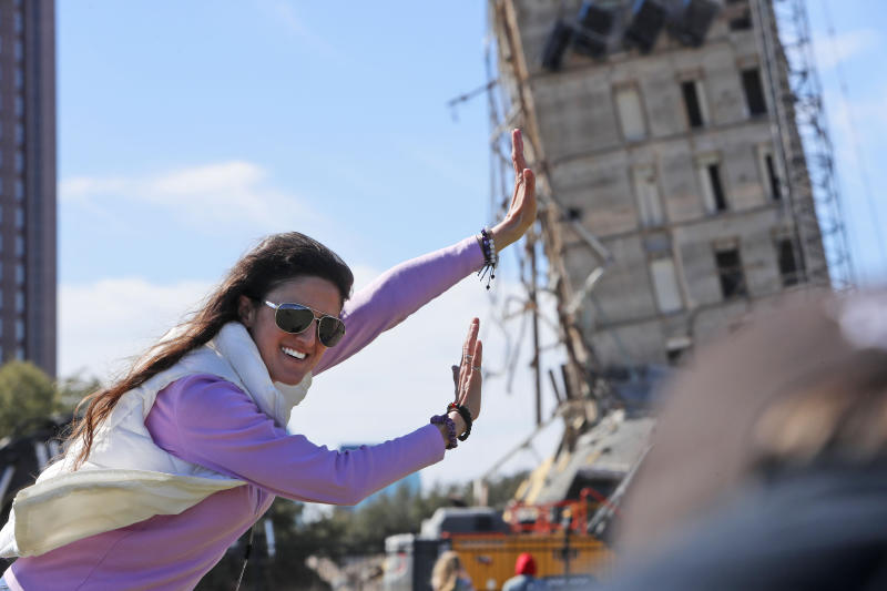 "Megan Dority poses for a photo with the so called ""Leaning Tower of Dallas"" as a crew works to topple the structure north of downtown Dallas, Monday, Feb. 24, 2020. The still standing structure is part of an 11-story building that found a second life online after surviving a first demolition attempt. The former Affiliated Computer Services building inspired jokes and comparisons to Italy's Leaning Tower of Pisa when a Feb. 16 implosion failed to bring down its core. The company that engineered the blast said some explosives did not go off. (AP Photo/LM Otero)"