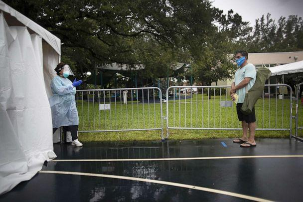 PHOTO: Dr. Jacqueline Delmont, Chief Medical Officer of SOMOS Community Care, asks Eddie Mena to move forward into the medical tent to be tested for COVID-19 at a testing site, July 22, 2020, in Miami Lakes, Fla. (Joe Raedle/Getty Images)