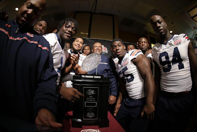 Auburn players pose with The Coaches' Trophy during media day for the NCAA BCS National Championship college football game Saturday, Jan. 4, 2014, in Newport Beach, Calif. Florida State plays Auburn on Monday, Jan. 6, 2014. (AP Photo/Chris Carlson)