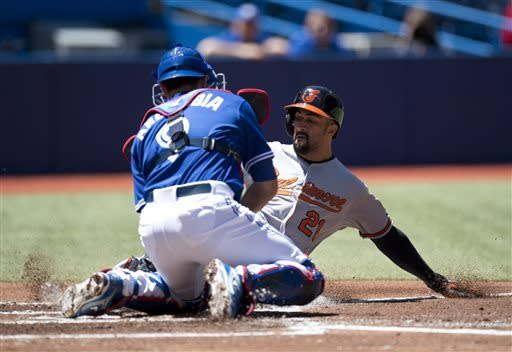 Toronto Blue Jays catcher J.P. Arencibia tags out Baltimore Orioles baserunner Nick Markakis at home during first inning MPB American League baseball action in Toronto, Sunday, May 26, 2013. Markakis was trying to score on a double by Adam Jones. (AP Photo\THE CANADIAN PRESS, Frank Gunn)