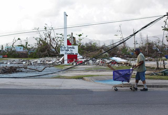 "<p>A man pushes a shopping cart past downed cables after Hurricane Maria hit the island in September, in Humacao, Puerto Rico, Oct. 20, 2017. The writing in the back reads ""Puerto Rico will rise."" (Photo: Alvin Baez/Reuters) </p>"