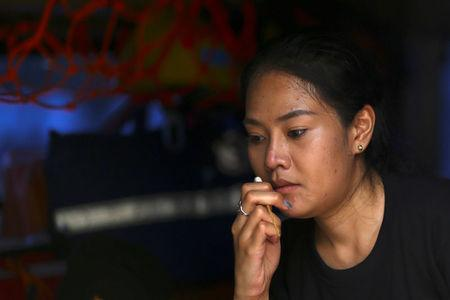 A mourner sniffs ammonia-soaked cotton wool handed out by medical rescue teams to help prevent fainting as she waits to pay her respects to Thailand's late King Bhumibol Adulyadej at the Grand Palace in Bangkok, Thailand, October 15, 2016. REUTERS/Athit Perawongmetha