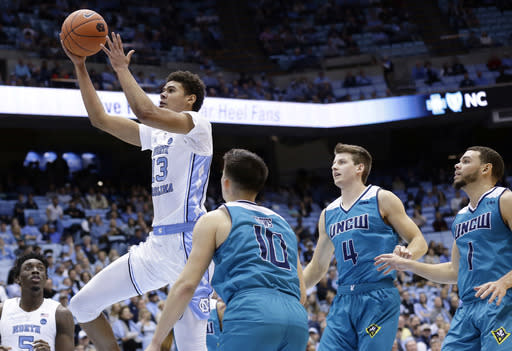 North Carolina's Cameron Johnson (13) drives to the basket while UNC Wilmington's Kai Toews (10), Shawn O'Connell (4) and Jaylen Fornes (1) defend during the first half of an NCAA college basketball game in Chapel Hill, N.C., Wednesday, Dec. 5, 2018. (AP Photo/Gerry Broome)