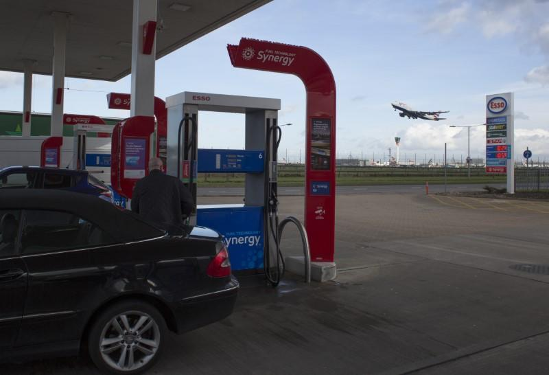 FILE PHOTO: A man fills his car with fuel at an Esso service station at Heathrow airport