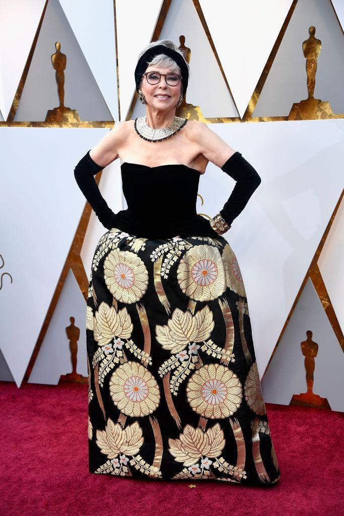 """<p>Rita Moreno, 86, chose a vintage gown with <a rel=""""nofollow"""" href=""""https://www.yahoo.com/lifestyle/rita-moreno-rewears-oscars-gown-235700975.html"""" data-ylk=""""slk:special meaning;outcm:mb_qualified_link;_E:mb_qualified_link;ct:story;"""" class=""""link rapid-noclick-resp yahoo-link"""">special meaning</a> for her night at the 2018 Academy Awards. The gown is the very same one that she wore to the Oscars 56 years ago, when she won Best Actress in a Supporting Role in 1961's <i>West Side Story</i>. """"I would think it would tarnish!"""" Moreno told Ryan Seacrest on the red carpet. But no, the dress was still golden on the radiant star. (Photo: Getty Images) </p>"""