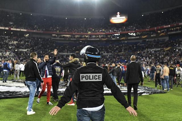 Police stand on the pitch after Besiktas' and Lyon's supporters fought before the UEFA Europa League first leg quarter final football match April 13, 2017, at the Parc Olympique Lyonnais stadium in Decines-Charpieu (AFP Photo/JEFF PACHOUD)