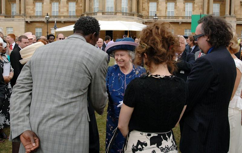 Queen Elizabeth II meets guests (left to right) Linford Christie, Helena Bonham Carter and Tim Burton at a garden party to mark 50 years of the Duke of Edinburgh's award scheme at Buckingham Palace. (Photo by Steve Parsons - PA Images/PA Images via Getty Images)