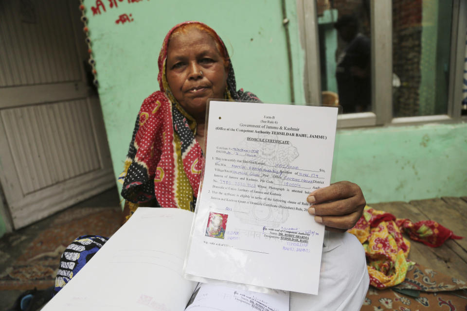 Krishna Singh shows her domicile certificate in Jammu, India, July 27, 2020. A year after India ended disputed Kashmir's semi-autonomous status and downgraded it to a federally governed territory, authorities have begun issuing residency and land ownership rights to outsiders for the first time in almost a century. Documents accessed and reviewed by The Associated Press show at least 60,000 have gained residency in the last two months including Hindu refugees, Gurkha soldiers and bureaucrats. (AP Photo/Channi Anand)