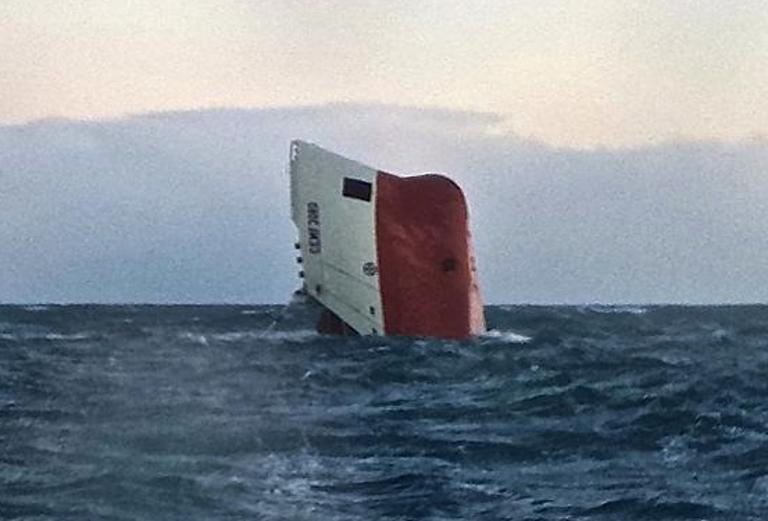 The upturned hull of cargo vessel Cemfjord pictured in the sea 15 miles from Wick in northeast Scotland on January 3, 2015