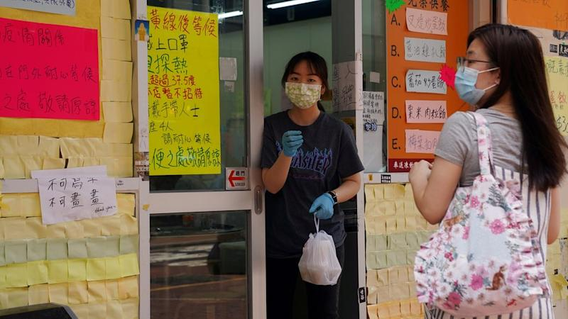 A staff member wearing a face mask following the coronavirus disease (Covid-19) outbreak hands takeaway food to a customer outside a restaurant in Hong Kong, China