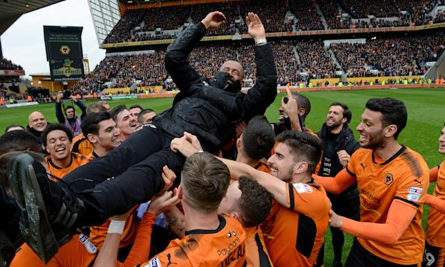 The Wolves players celebrate promotion to the Premiership by launching Nuno Espírito Santo into the air.