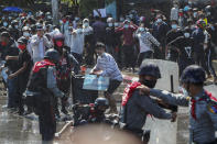 Protesters run after police shot warning shots and used water cannon to disperse them during a protest in Mandalay, Myanmar, Tuesday, Feb. 9, 2021. In the month since Feb. 1 coup, the mass protests occurring each day are a sharp reminder of the long and bloody struggle for democracy in a country where the military ruled directly for more than five decades. (AP Photo)