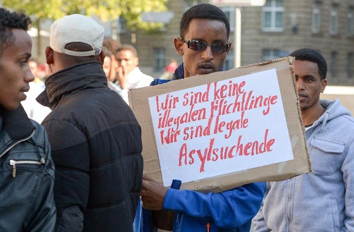 """A refugee from Eritrea holds a poster reading """"We are not illegal refugees - we are legal asylum-seekers"""" during a demonstration against the German procedure for granting asylum on October 2, 2015 in Erfurt, eastern Germany (AFP Photo/Peter Endig)"""
