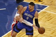 Orlando Magic center Nikola Vucevic (9) keeps the ball away from Detroit Pistons center Mason Plumlee in the first half during an NBA basketball game, Sunday, Feb. 21, 2021, in Orlando, Fla. (AP Photo/Joe Skipper)