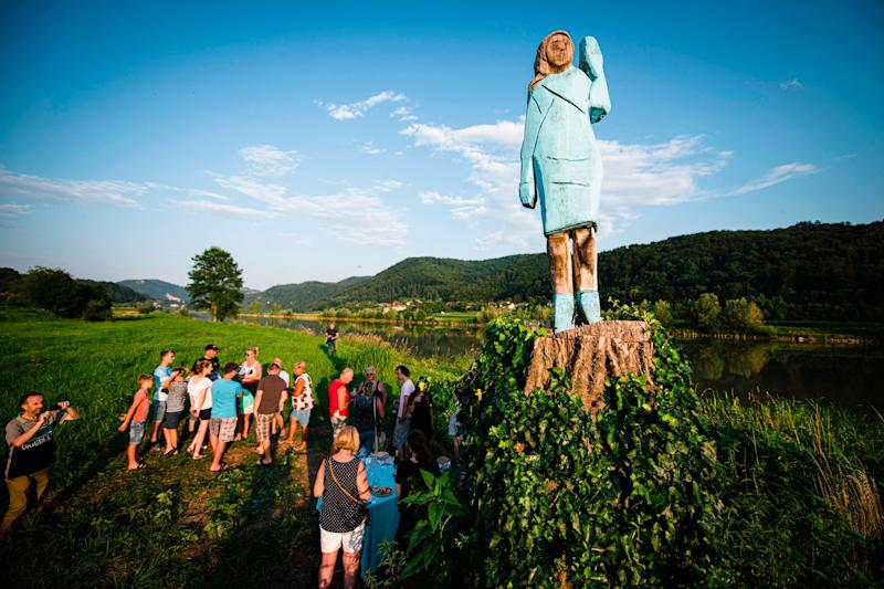 People gather around what conceptual artist Ales 'Maxi' Zupevc claims is the first ever monument of Melania Trump, set in the fields near the town of Sevnica, US First Ladys hometown, during a small inauguration celebration on July 5, 2019.