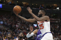 New York Knicks guard Reggie Bullock (25) gets past Utah Jazz center Rudy Gobert for a shot during the second quarter of an NBA basketball game Wednesday, Jan. 8, 2020, in Salt Lake City. (AP Photo/Chris Nicoll)