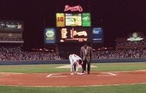 FILE - In this April 4, 1997, file photo, former Atlanta Braves great Hank Aaron looks on as pitcher Tom Glavine places down home plate from Atlanta Fulton County Stadium on top of the plate at Turner Field before the Braves opened their new home against the Chicago Cub in Atlanta. To baseball fans, opening day is an annual rite of springthat evokes great anticipation and warm memories. This year's season was scheduled to begin Thursday, March 26, 2020, but there will be no games for a while because of the coronavirus outbreak. (AP Photo/John Bazemore, File)