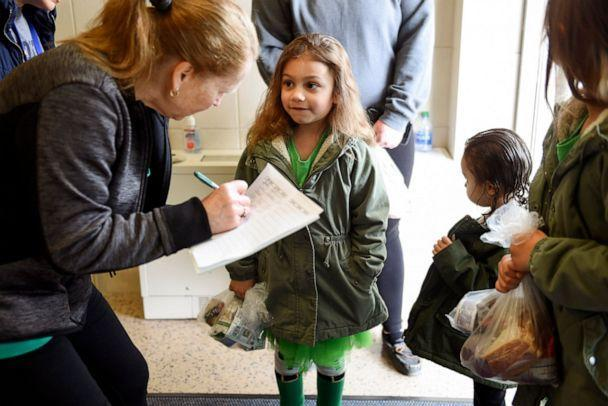 PHOTO: A member of the food service staff records the names of children who are picking up lunches and educational packets at the West Reading Elementary Center in West Reading, Pa., March 17, 2020. (Reading Eagle/MediaNews Group via Getty Images, FILE)