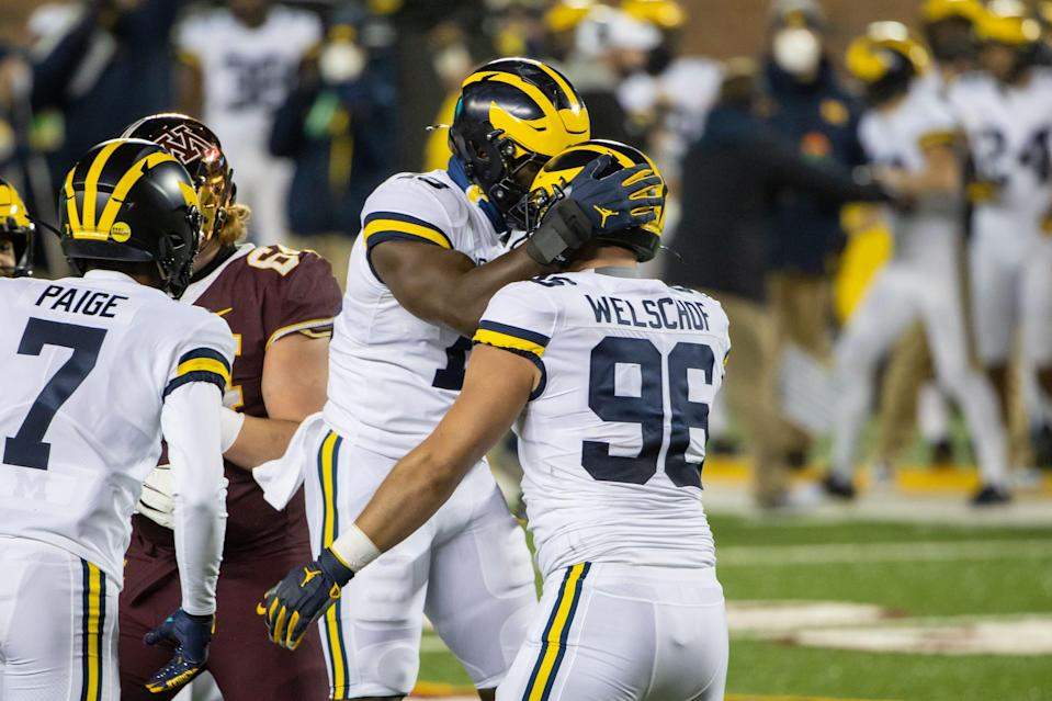 Michigan Wolverines defensive lineman Julius Welschof (96) celebrates with defensive lineman Kwity Paye (19) after sacking Minnesota quarterback Tanner Morgan in the first quarter at TCF Bank Stadium, Oct. 24, 2020.