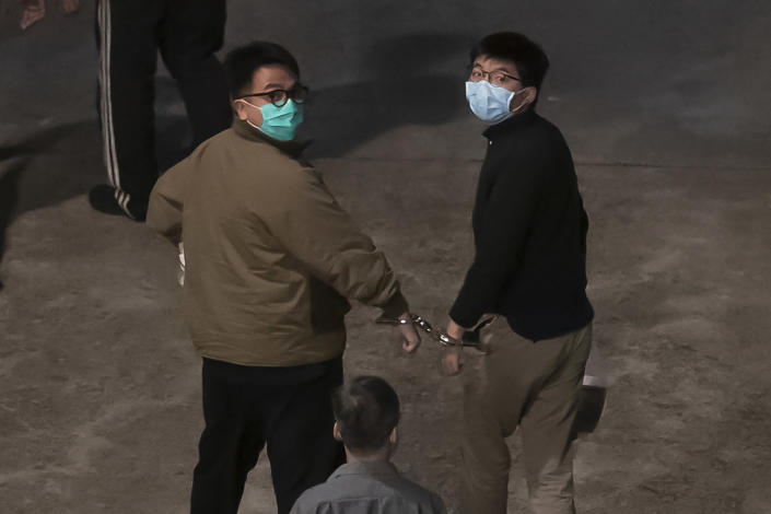 Hong Kong activists Joshua Wong, right, and Ivan Lam, left, are escorted by Correctional Services officers to prison, in Hong Kong, Wednesday, Dec. 2, 2020. Three prominent Hong Kong pro-democracy activists, Wong, Lam, and Agnes Chow were sentenced to jail Wednesday for a protest outside police headquarters as authorities step up a crackdown on opposition to tighter Chinese control of the territory. (AP Photo/Kin Cheung)