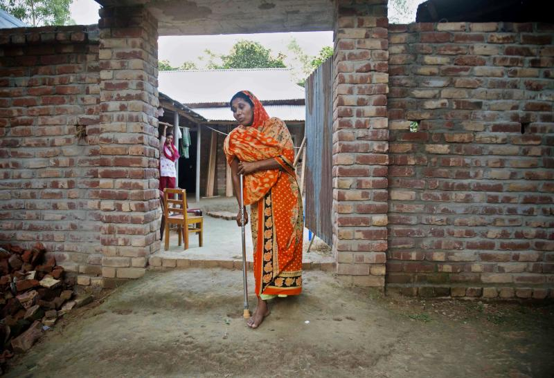 "In this photo taken Monday, May 21, 2013, Hawa Begum walks with a crutch outside the family home in Tekani village in far northwestern Bangladesh. Hawa was severely injured when she jumped out of a fifth-floor window to escape the flames that consumed the Tazreen garment factory last November. Her 18-year-old daughter Moushimi was one of the 112 workers who did not survive the fire. ""I tried to go to my daughter, but there was no way,"" Hawa recalled. ""The gates on each floor were locked. There was smoke everywhere."" (AP Photo/Ismail Ferdous)"