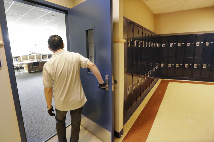 A school janitor opens the door to a staff room inside Bothell High School, closed for the day, Thursday, Feb. 27, 2020, in Bothell, Wash. The suburban Seattle school was closed Thursday after a staffer's family member was placed in quarantine for showing symptoms of possibly contracting the new virus that started in China - an action health officials say is unnecessary. The school will be cleaned and disinfected while students stay home. (AP Photo/Elaine Thompson)