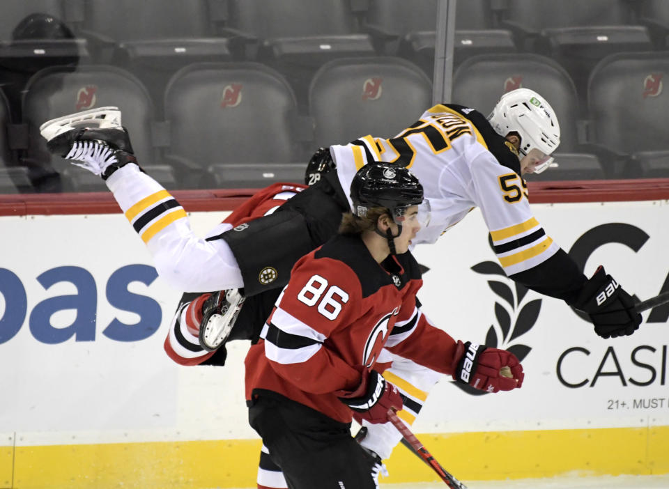 Boston Bruins defenseman Jeremy Lauzon (55) attempts to squeeze between New Jersey Devils center Janne Kuokkanen, rear, and center Jack Hughes (86) during the first period of an NHL hockey game Saturday, Jan. 16, 2021, in Newark, N.J. (AP Photo/Bill Kostroun)