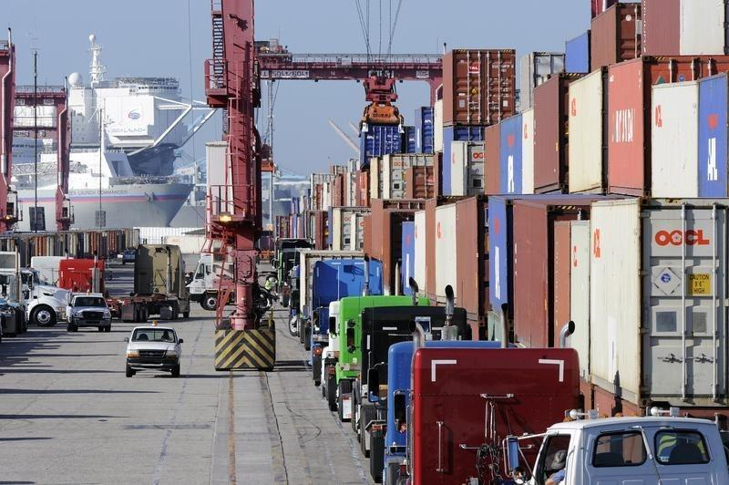 Semi trucks line up to pick up shipping containers at the Port of Long Beach