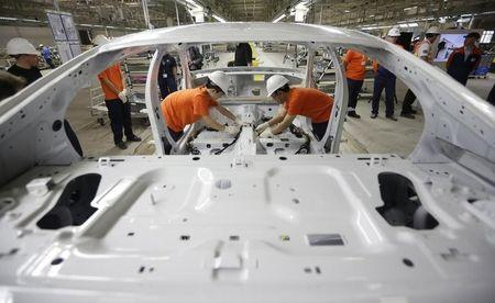 Workers assemble parts of a Volvo car at an assembly line of the new Volvo automobile manufacturing plant in Chengdu