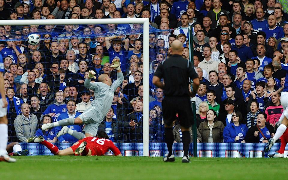 Everton's Australian midfielder Tim Cahill (R) scores past Liverpool's Spanish goalkeeper Pepe Reina during their English Premier League football match against Everton at Goodison Park in Liverpool, north-west England, - PAUL ELLIS/AFP