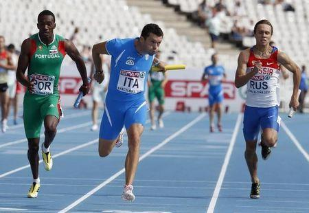 Italy's Maurizio Checcucci (C), Portugal's Yazaldes Nascimento (L) and Russia's Vyacheslav Kolesnichenko sprint to the finish during the men's 4 x 100 metres relay heats at the European Athletics Championships in Barcelona July 31, 2010. REUTERS/Sergio Perez (SPAIN - Tags: SPORT ATHLETICS)
