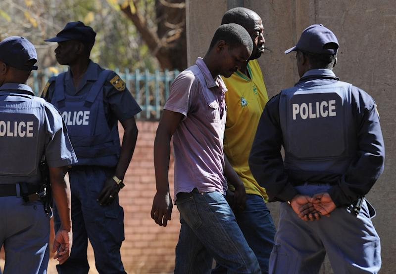 Police keep an eye on arrested mineworkers as they arrive at a court in Ga-Rankuwa, north of Pretoria, South Africa, Monday Aug. 20, 2012. The miners are among 259 expected to be charged with public violence at the Lonmin Platinum Mine where police shot and killed 34 striking workers last week. (AP Photo)
