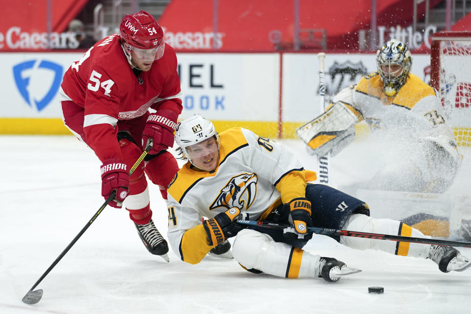 Nashville Predators center Mikael Granlund (64) loses his edge as Detroit Red Wings right wing Bobby Ryan (54) defends in the second period of an NHL hockey game Thursday, Feb. 25, 2021, in Detroit. (AP Photo/Paul Sancya)