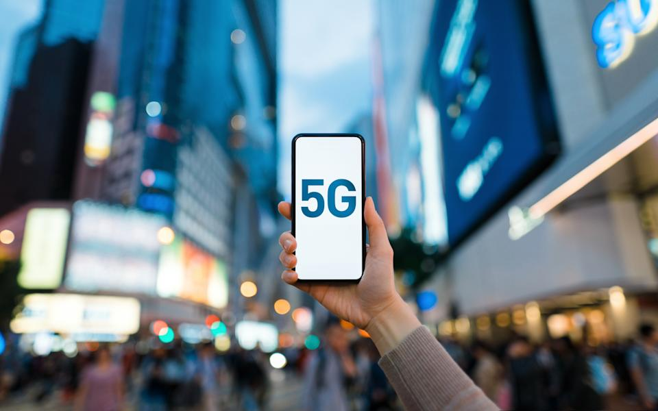 Woman's hand using smartphone against illuminated financial district in the city, with the concept of 5G communications technology
