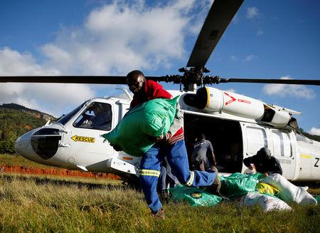 People receive food aid after Cyclone Idai from a helicopter drop at a distribution centre at Ngangu in Chimanimani, Zimbabwe, March 22, 2019. REUTERS/Philimon Bulawayo
