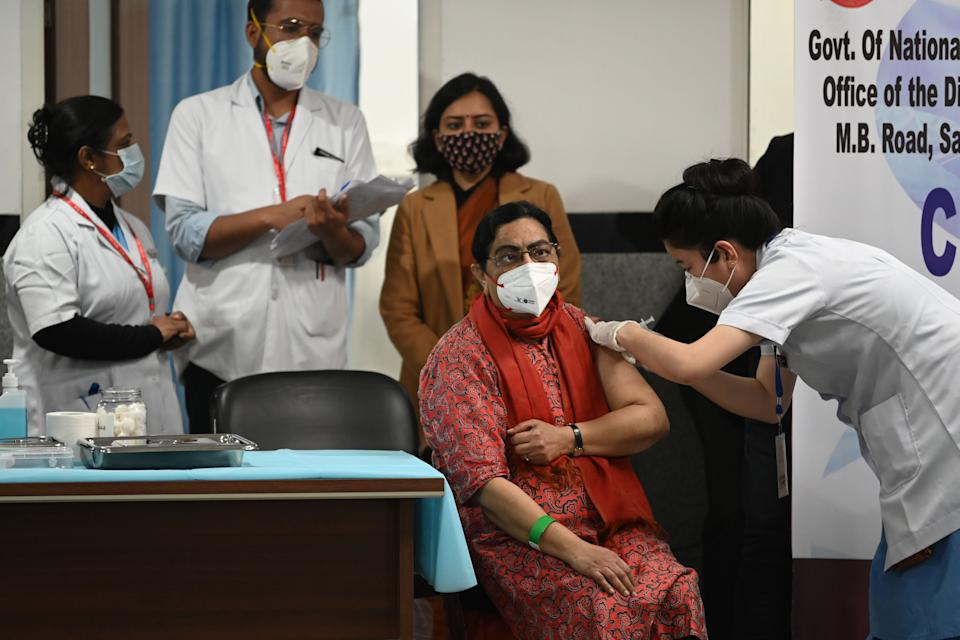 A medical worker inoculates a colleague with a Covid-19 coronavirus vaccine at the All India Institute of Medical Science (AIIMS) in New Delhi in January 16, 2021. (Photo by Sajjad HUSSAIN / AFP) (Photo by SAJJAD HUSSAIN/AFP via Getty Images)