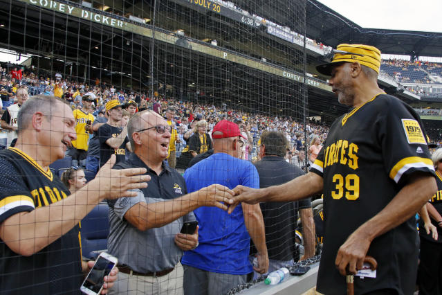 Dave Parker, a member of the 1979 Pittsburgh Pirates World Championship team, right, greets fans before a pre-game ceremony honoring the team before a baseball game between the Pittsburgh Pirates and the Philadelphia Phillies in Pittsburgh, Saturday, July 20, 2019. (AP Photo/Gene J. Puskar)