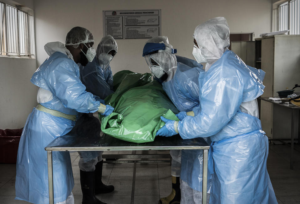 People prepare the body of a person who died from Covid-19 in Johannesburg. Source: AAP