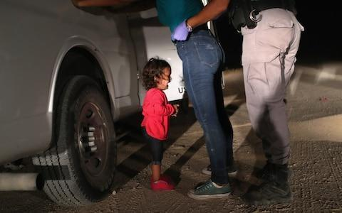 "The UN human rights chief on Monday urged Washington to stop separating migrant children from their parents at the US border, describing the policy as ""unconscionable"". ""The thought that any state would seek to deter parents by inflicting such abuse on children is unconscionable,"" Zeid Ra'ad Al Hussein said as he opened a session of the UN Human Rights Council in Geneva. The ""zero-tolerance"" border security policy implemented by President Donald Trump's administration has sparked global outrage. Images released on Monday morning showed segregated children detained in cages inside a warehouse in Texas, after journalists were given access for the first time. It came as senior Republicans continued to call into question the hardline policy. Melania Trump, the first lady, also appeared to question the treatment of migrants. In a statement last night she said she ""hates to see children separated from their families"", while the former first lady Laura Bush said the policy ""breaks my heart"". A two-year-old Honduran asylum seeker cries as her mother is searched and detained near the US-Mexico border on June 12 Credit: John Moore/Getty The government has said that during one recent six-week period nearly 2,000 minors were separated from their parents or adult guardians. The number of separations has jumped since early May, when Attorney General Jeff Sessions announced that all migrants illegally crossing the US border with Mexico would be arrested, regardless of whether the adults were seeking asylum. Since children cannot be sent to the facilities where their parents are held, they are separated. Zeid quoted the American Association of Pediatrics as describing the practice as ""government-sanctioned child abuse"" which may cause ""irreparable harm,"" with ""lifelong consequences"". ""I call on the United States to immediately end the practice of forcible separation of these children,"" he said, urging Washington to ratify the Convention of the Rights of the Child. The UN said that segregating children amounted to 'abuse' The US is the only country that has not ratified the convention. Ratification, Zeid said, would ""ensure that the fundamental rights of all children, whatever their administrative status, will be at the centre of all domestic laws and policies."" Zeid's address at the start of the 38th session of the UN Human Rights Council marks his last address to the body before he is due to step down at the end of August. The session kicked off under a cloud of growing US criticism of the council. Diplomatic sources said there was a risk that Washington may withdraw from the council altogether. The US Border Patrol on Sunday allowed reporters to briefly visit the facility where it holds families arrested at the border. Inside an old warehouse in South Texas, hundreds of children wait in a series of cages created by metal fencing. One cage had 20 children inside. Scattered about are bottles of water, bags of chips and large foil sheets intended to serve as blankets. Migrants caught trying to enter the US illegally are being separated from their children Credit: LOREN ELLIOTT/AFP One teenager told an advocate who visited that she was helping care for a young child she didn't know because the child's aunt was somewhere else in the facility. She said she had to show others in her cell how to change the girl's diaper. Mr Trump himself has also said he ""hates to see separation of parents and children"" and has accused Democrats of pursuing a ""horrible and cruel legislative agenda"". The Border Patrol said close to 200 people inside the facility were minors unaccompanied by a parent. Another 500 were ""family units,"" parents and children. Many adults who crossed the border without legal permission could be charged with illegal entry and placed in jail, away from their children. Reporters were not allowed by agents to interview any of the detainees or take photos. Stories have spread of children being torn from their parents' arms, and parents not being able to find where their kids have gone. A group of congressional lawmakers visited the same facility on Sunday and were set to visit a longer-term shelter holding around 1,500 children - many of whom were separated from their parents. ""Those kids inside who have been separated from their parents are already being traumatised,"" said Democratic Sen. Jeff Merkley of Oregon, who was denied entry earlier this month to children's shelter. ""It doesn't matter whether the floor is swept and the bedsheets tucked in tight."" Children in custody are forced to sleep on mattresses with foil covers In Texas' Rio Grande Valley, the busiest corridor for people trying to enter the US, Border Patrol officials argue that they have to crack down on migrants and separate adults from children as a deterrent to others. ""When you exempt a group of people from the law ... that creates a draw,"" said Manuel Padilla, the Border Patrol's chief agent here. ""That creates the trends right here."" Agents running the holding facility - generally known as ""Ursula"" for the name of the street it's on - said everyone detained is given adequate food, access to showers and laundered clothes, and medical care. People are supposed to move through the facility quickly. Under US law, children are required to be turned over within three days to shelters funded by the Department of Health and Human Services. Padilla said agents in the Rio Grande Valley have allowed families with children under the age of 5 to stay together in most cases. An advocate who spent several hours in the facility on Friday said she was deeply troubled by what she found. Michelle Brane, director of migrant rights at the Women's Refugee Commission, met with a 16-year-old girl who had been taking care of a young girl for three days. The teen and others in their cage thought the girl was two years old. ""She had to teach other kids in the cell to change her diaper,"" Brane said."
