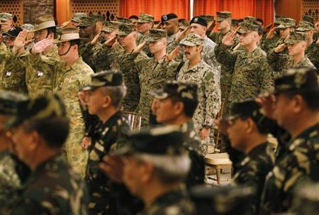 U.S. and Filipino military officers salute during the opening ceremony of the Balikatan 2014 Joint Exercise inside the AFP headquarters at Camp Aguinaldo in Quezon city, metro Manila