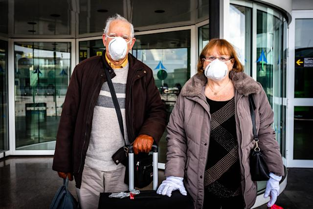 Arrivals at El Prat International Airport in Barcelona are pictured wearing masks on 19 March. Spain has had more than 17,300 confirmed cases since the outbreak was identified. (Getty Images)