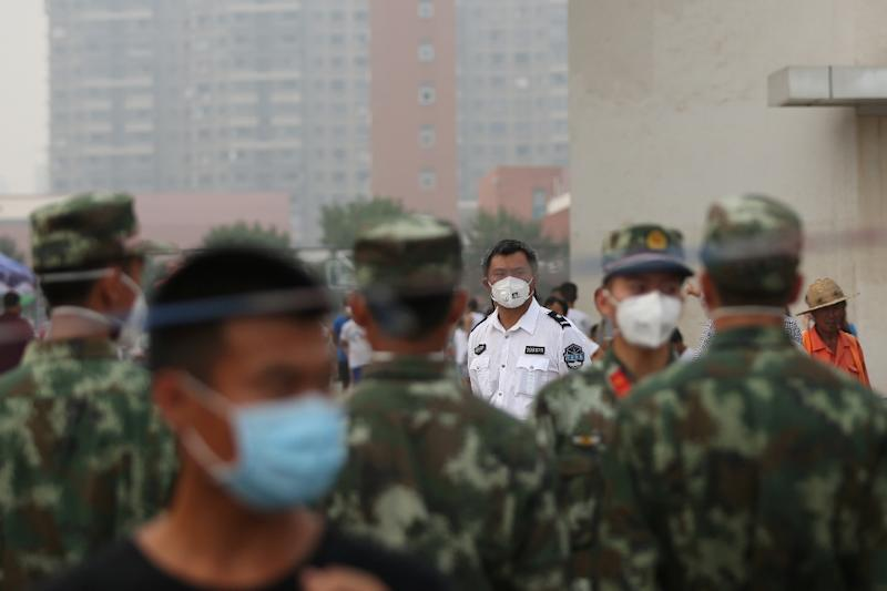 Volunteers and paramilitary soldiers wear masks as they stand on patrol outside a temporary shelter after the explosions in Tianjin on August 14, 2015 (AFP Photo/)