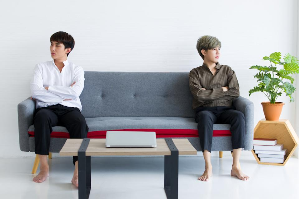 Gay couple sitting on the sofa bed with arms crossed and don't look at each other.