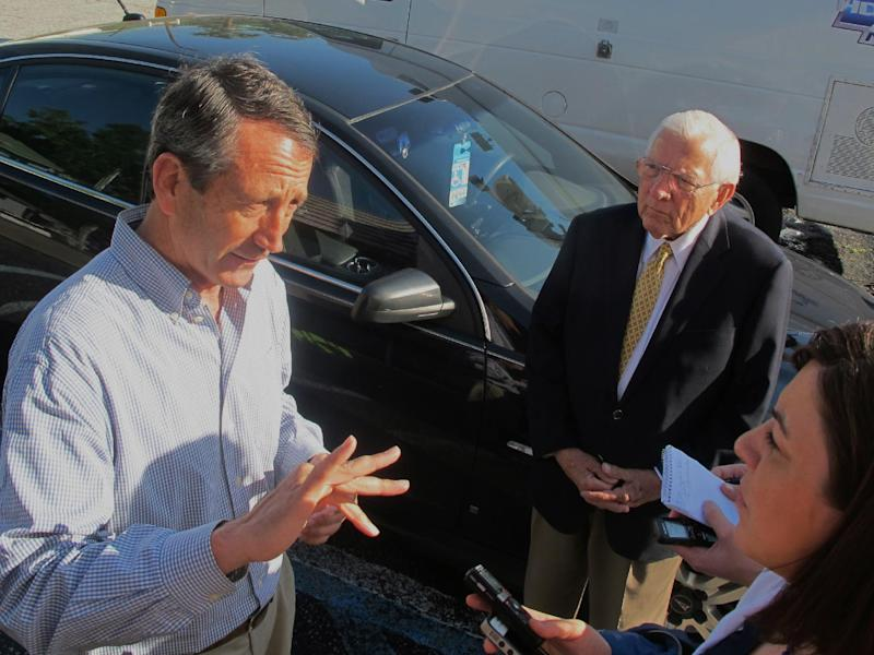 Mark Sanford speaks with a reporter as former S.C. Gov. Jim Edwards looks on during a campaign stop at a diner in Mount Pleasant, S.C., on Monday, May 6, 2012. Sanford faces Elizabeth Colbert Busch, the sister of comedian Stephen Colbert, in a special congressional election in the state's 1st District on Tuesday. (AP Photo/Bruce Smith)