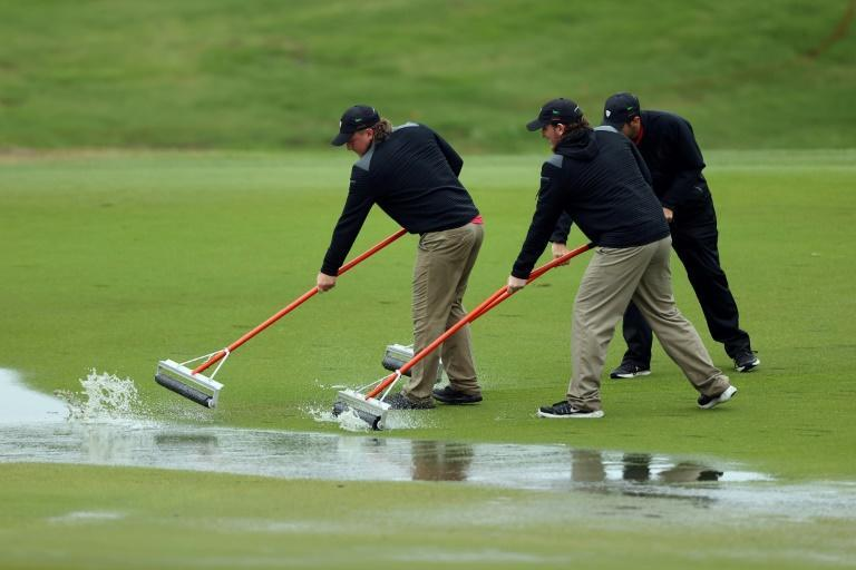 Groundskeepers prepare the course for competition after play was suspended in the final round of the Byron Nelson tournament due to inclement weather