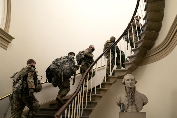 WASHINGTON, DC - JANUARY 13: Members of the National Guard wear protective masks while walking through the U.S. Capitol on January 13, 2021 in Washington, DC. Security has been increased throughout Washington following the breach of the U.S. Capitol last Wednesday, and leading up to the Presidential inauguration. (Photo by Stefani Reynolds/Getty Images)