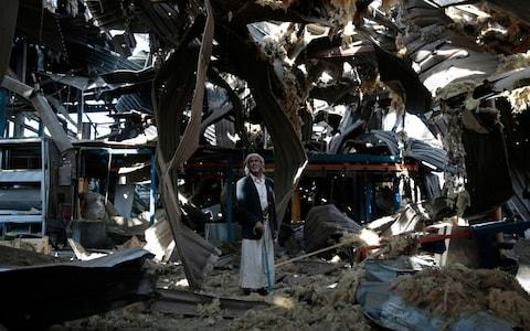<span>A man stands among the rubble of the Alsonidar Group's water pump and pipe factory after it was hit by Saudi-led airstrikes in Sanaa, Yemen</span> <span>Credit: AP </span>