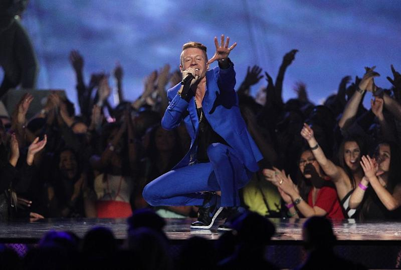 """FILE - In this April 14, 2013 file photo, Macklemore performs """"Can't Hold Us"""" at the MTV Movie Awards in Sony Pictures Studio Lot in Culver City, Calif. Macklemore & Ryan Lewis are top contenders at the Jan. 26, 2014, Grammy Awards, with seven nominations, including best new artist and song of the year for """"Same Love."""" Their debut album, """"The Heist,"""" is up for album of the year and best rap album, while the massive hit """"Thrift Shop"""" is nominated for best rap song and rap performance. The duo's other hit, """"Can't Hold Us,"""" will compete for best music video. (Photo by Matt Sayles/Invision /AP)"""