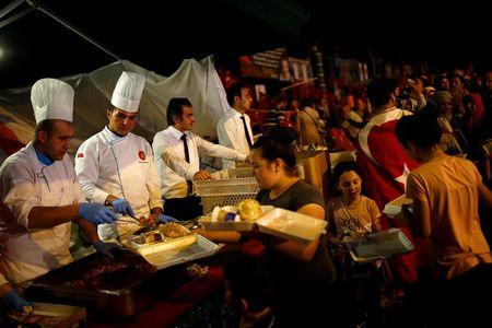 Cooks of the Presidential Palace serve food to people gathered in solidarity outside Turkish President Tayyip Erdogan's palace night after night since the July 15 coup attempt in Ankara, Turkey, July 27, 2016. REUTERS/Umit Bektas