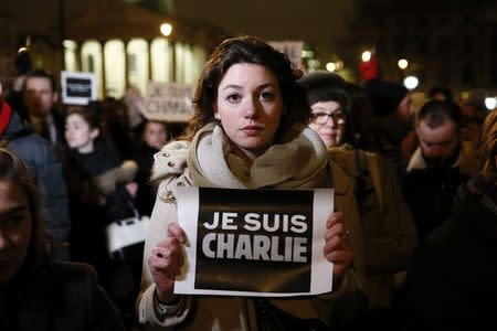 """A woman holds a placard that reads, """"I am Charlie"""", during a vigil to pay tribute to the victims of a shooting by gunmen at the offices of weekly satirical magazine Charlie Hebdo in Paris, at Trafalgar Square in London January 7, 2015. REUTERS/Stefan Wermuth"""